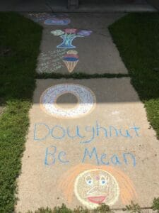"Photo of sidewalk chalk art. There is a drawing of a doughnut, and beneath it are the words ""Doughnut Be Mean,"" written in blue chalk. Beneath the text is a drawing of a person's face smiling."