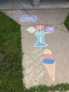 "This image captures sidewalk chalk art. In the top left corner, the words ""Just Keep Swimming"" are above a purple fish drawn in a fishbowl. Below this is a vase of water with three flowers in it. At the bottom of the image is an ice cream cone with three scoops of ice cream (blue, red, and yellow), with text to the left that says, ""I scream, you scream, we all do for ice cream."""