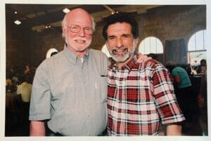 Ed Flahavan and Joe Errigo standing next to each other with an arm across each other's back. Both are smiling at the camera. Ed is wearing a gray short sleeve shirt and Joe is wearing a red-and-white plaid short sleeve shirt.