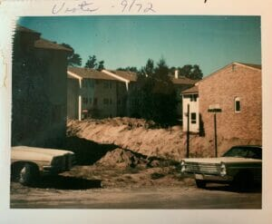 Photo of deep holes in ground with mounded dirt, surrounded by some other apartment buildings and the front and back of two old cars