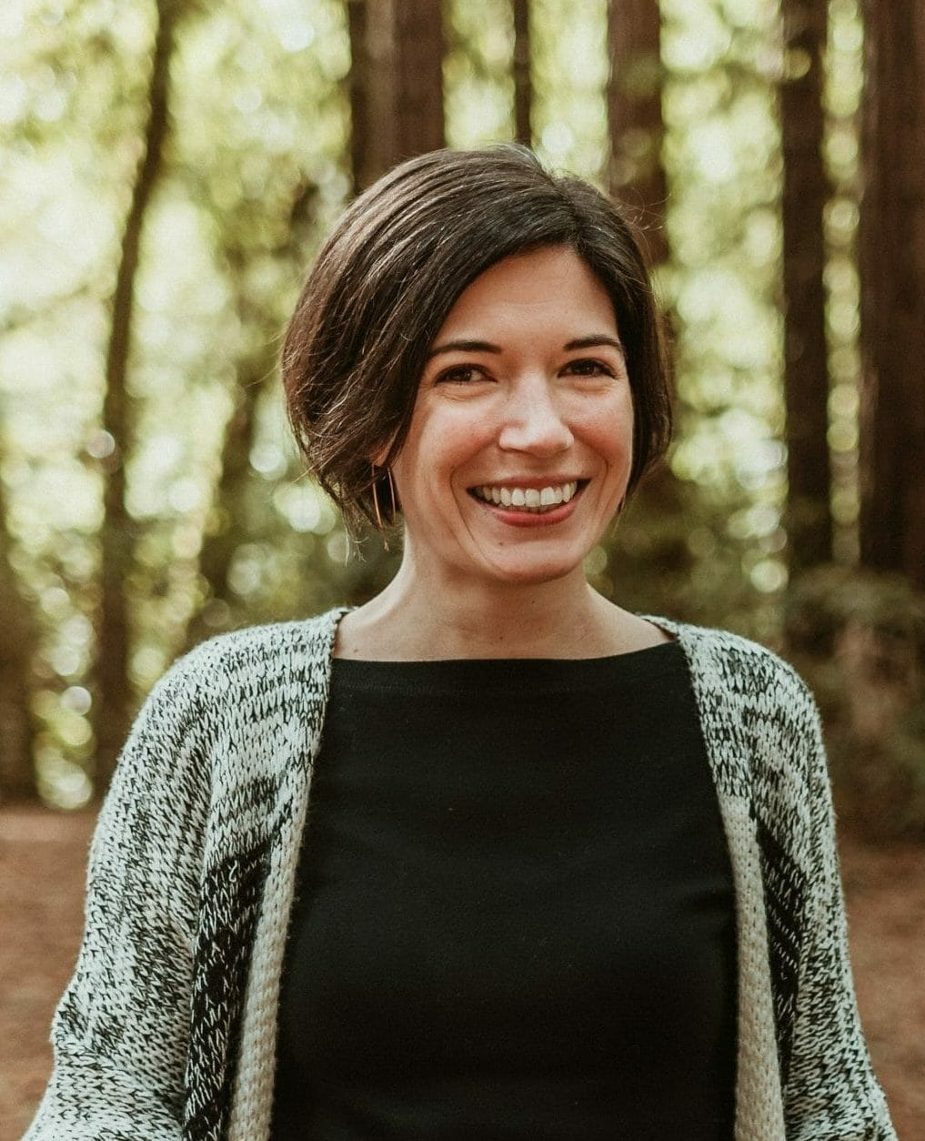 Meredyth stands outside with greenery and trees behind her, and smiles at the camera. She wears a black shirt and grey cardigan.